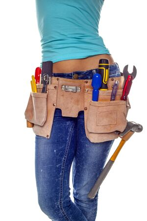 A woman wearing a DIY tool belt full of a variety of useful tools on a white background   photo
