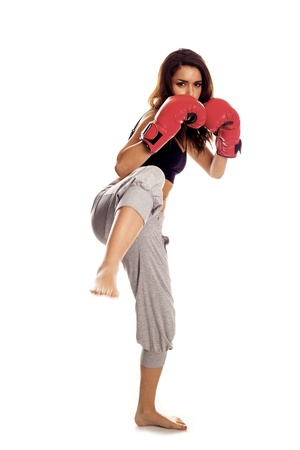 A female kick boxer wearing red gloves on a white background  photo