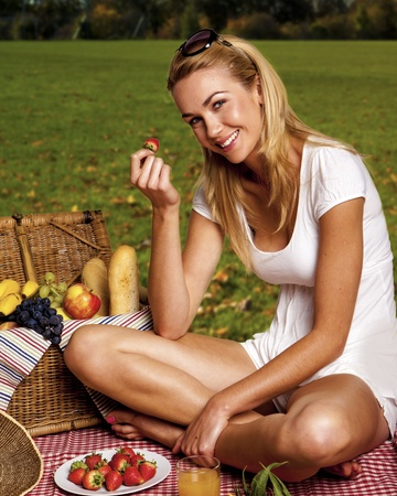 Beautiful blond woman enjoying a picknick outdoors. Stock Photo