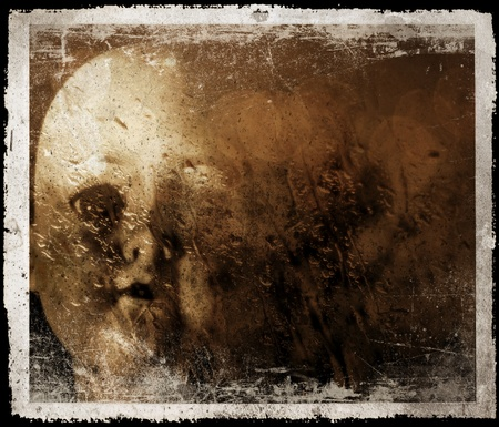 A spooky and disturbing image of a doll on a grunge and old photo effect