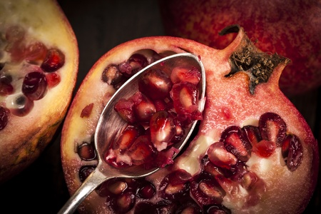 Pomegranate fruit on a old wooden table with a silver spoon  photo