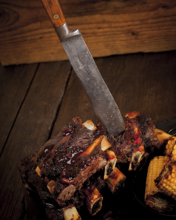 Beef ribs cooked on the barbeque and served with sweetcorn and a red wine souse  photo
