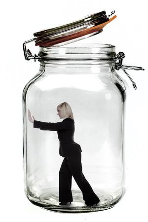 Businesswoman trapped inside a transparent glass jar