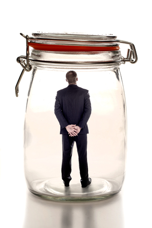 A businessman sitting inside a glass jar as business concept for feeling trapped in the workplace