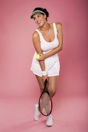 A beautiful woman enjoying the great game of tennis on a pink background  photo