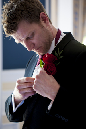 A handsome groom is trying his best to fit his rose to his jacket  photo