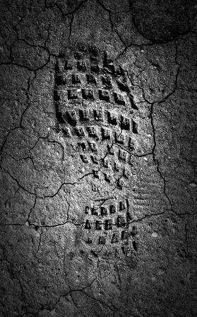 Forgotten footprint in the moonlight  A abstract image of a black and white image of a boot print in dried out mud  photo