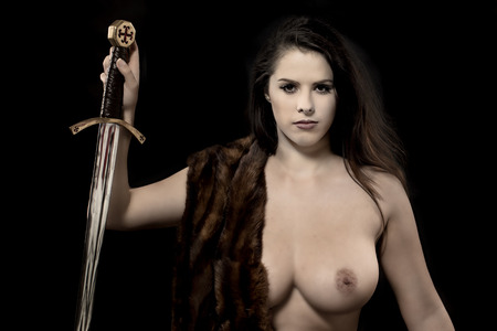 A beautiful topless woman holding a sword over a black background