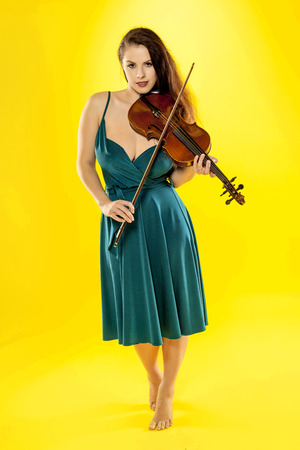 A beautiful female violinist over a yellow background  photo