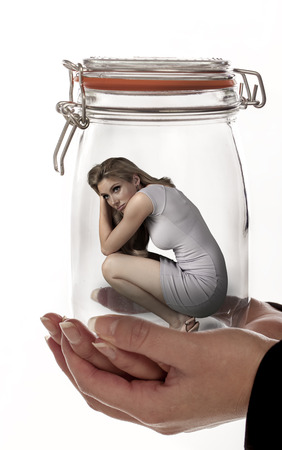 Blond woman trapped in a glass jar being hold by woman hands. photo