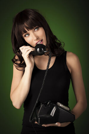 A beautiful woman talking on a old retro phone over a green background. photo