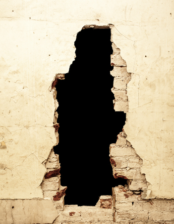 Dilapidated wall with black hole that can be removed. photo