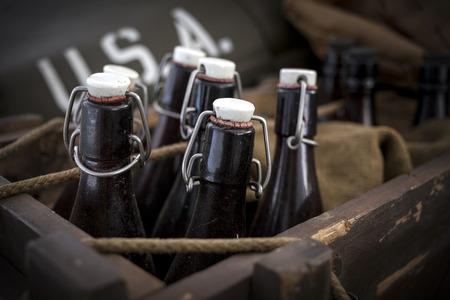 Old vintage beer bottles in a wooden crate.