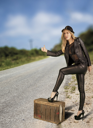 hitch hiker: Beautiful female hitch hiker alone on a lonely road. Stock Photo