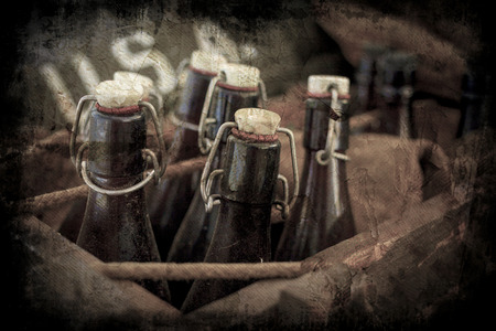 Old vintage beer bottles in a wooden crate with a grunge effect. Stock Photo