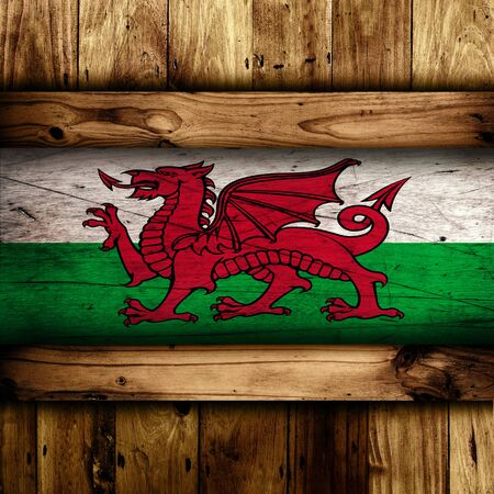 welsh flag: Abstract Welsh flag over a wooden background. Stock Photo