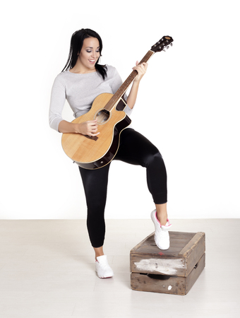 Young female busker sitting on a wooden box playing her guitar for money.