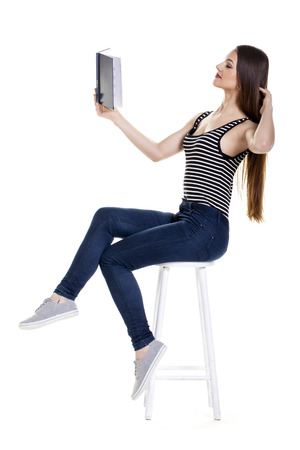 Young woman reading a book over a white background.