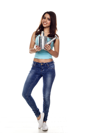 Beautiful and fashion young woman holding a watering can.