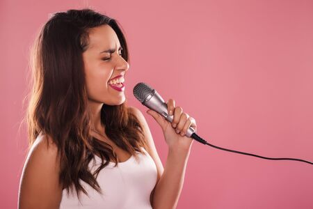 temptative: Portrait of a charming and beautiful woman singing with microphone in studio over pink background.