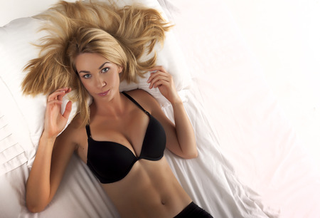 A very sexy blond woman wearing a black bra on a white background. Sexy blond woman.