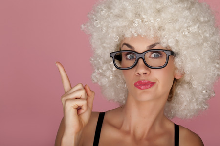 funny hair: Playful and funny woman wearing a curly wig on a pink background. Having fun. Stock Photo