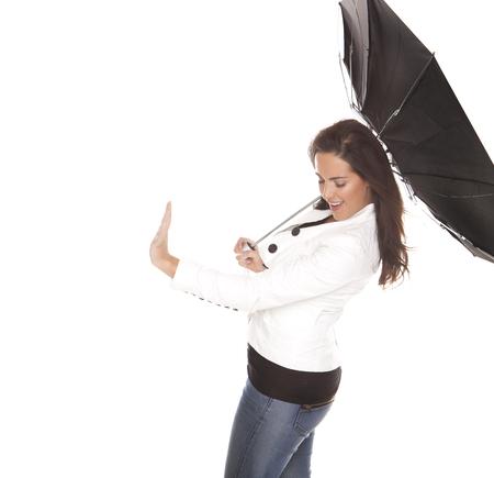 白い背景に強い風の黒傘につかまって女性。