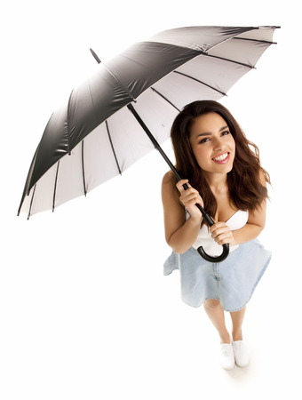 Young happy woman with umbrella over white background. Standard-Bild