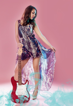 Fashion girl with guitar playing hard-rock over a pink background. Guitar beauty. Standard-Bild