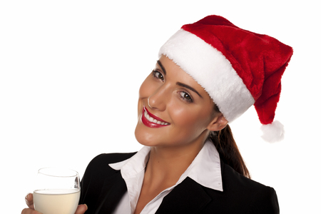 female christmas: A beautiful young businesswoman wearing a Santa hat on a white background. Businesswoman at a Christmas party.