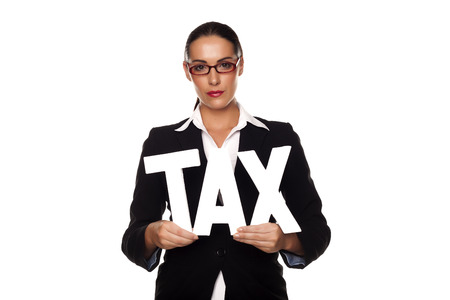 tax consultants: A businesswoman holding letters to spell out tax as a pay your tax concept. Pay your tax.