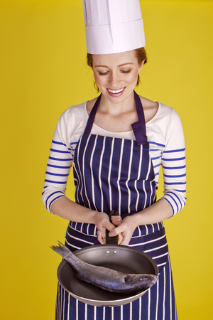 Beautiful chef over a yellow background. photo