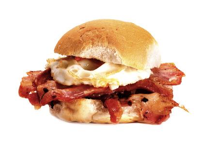 A delicious bacon and egg bun on a white background. Bacon and egg bun. Foto de archivo