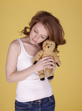Beautiful young woman holding and kissing here small toy bear. Always together the two of us. photo
