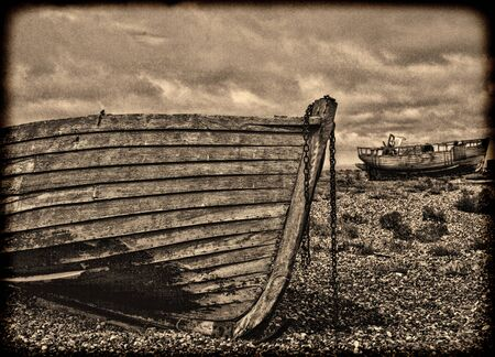 Abstract vintage grainy sepia image of old wooden fishing boats a stony beach.