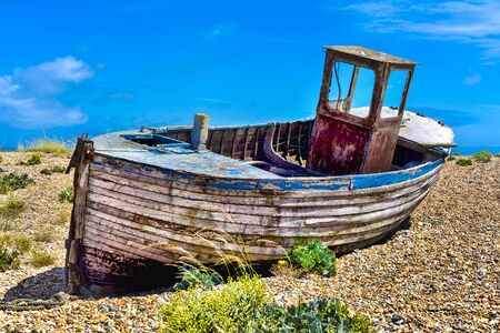 Old wooden fishing boat on a pebble beach. Standard-Bild