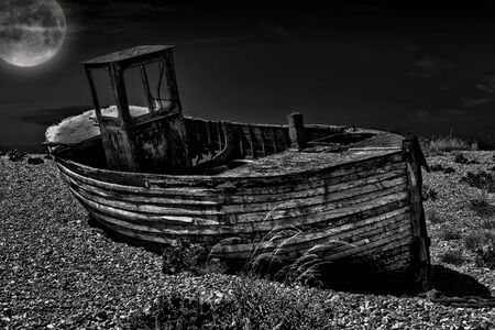Vintage fishing boat. An old abandoned fishing boat stranded on a beech in black and white. Standard-Bild
