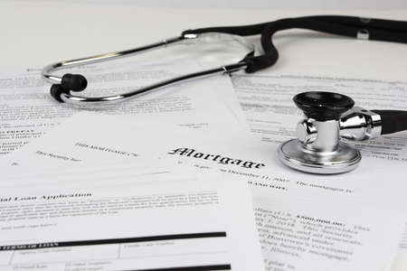 foreclose: Mortgage documents with stethoscope