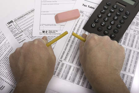 deduct: Hands breaking pencil in frustration over tax forms Stock Photo