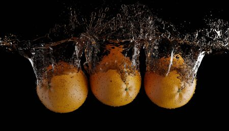 Splashing fruit on water. Fresh Fruit orange being shot as they submerged under water on black background