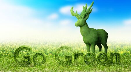 Isolated Go Green field letter and grass deer on blurry blue sky background Banco de Imagens