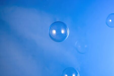 Transparent air soap foam bubble isolated on blue background