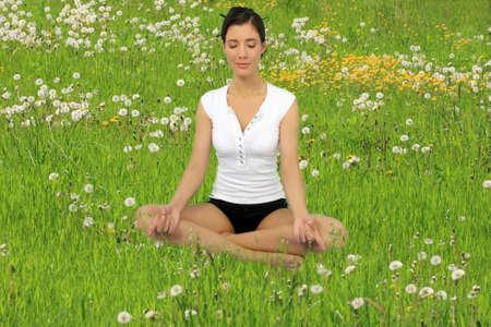 Girl meditation on a flower meadow Фото со стока