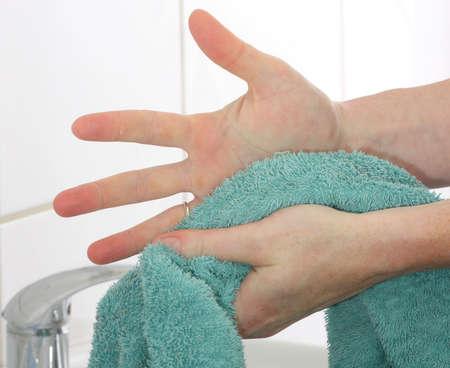 manos limpias: Secado de las manos con una toalla de