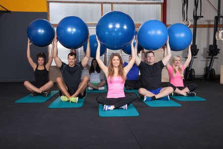 Medicine ball fitness training - sports team sitting on yoga mat Фото со стока