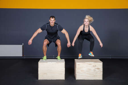 cross: Man and woman jumping on a box - cross fit Stock Photo