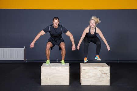Man and woman jumping on a box - cross fit Фото со стока
