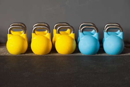 colorful kettlebells in a row in a gym Фото со стока