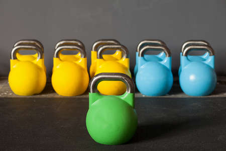 gym dress: colorful kettlebells in a row in a gym - focus on the front kettle bell Stock Photo