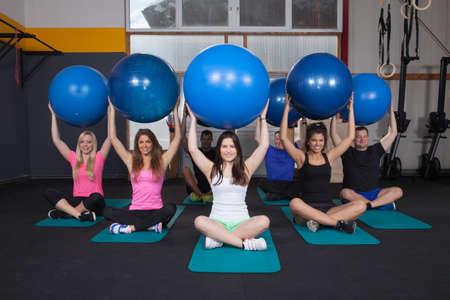 sport team: Geneesmiddel bal fitness training - sportteam zittend op yogamat